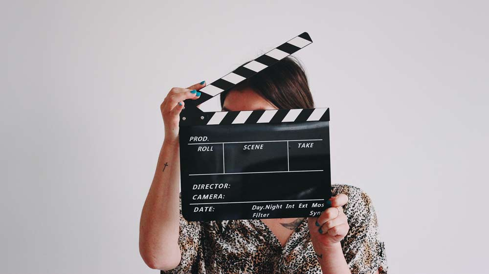 Clapperboard in front of woman's face